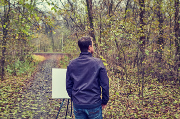 Man painting on canvas in forest