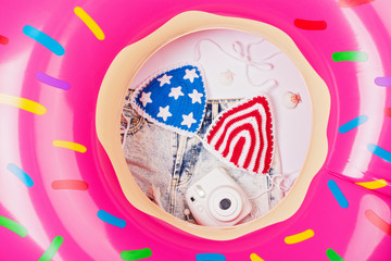 Inflatable donut float, American flag crochet bikini, camera and shorts. Summer vacation holiday concept