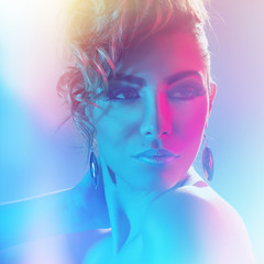 Beautiful stylish woman with professional hair and makeup. Creative dramatic pink and blue lights.