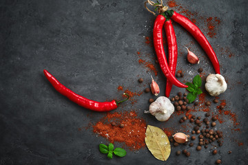 Food cooking background with chili peppers, garlic and spices on dark stone table.