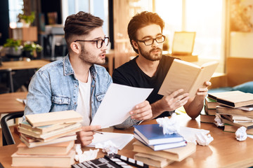 Two freelancer men reading notes at laptop at desk surrounded by books.
