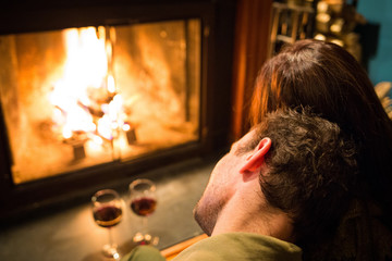 Couple sitting at warm fireplace with wine
