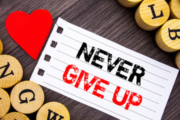 Handwriting text showing Never Give Up. Conceptual photo Motivation Quote For Success Achievement Challenge written on tear note paper sticky note on the wooden background with heart.