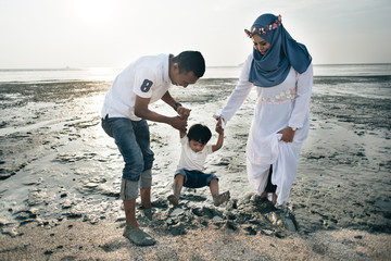 happy asian family wearing casual and playing with mud at the muddy beach located in pantai remis, kuala selangor, selangor, malaysia