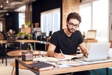 Freelancer bearded man taking notes at laptop sitting at desk.