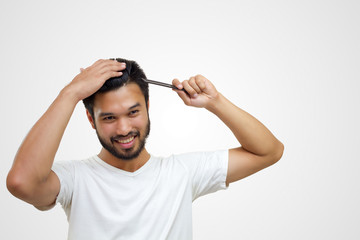 people concept - smiling young man brushing hair with comb on white background