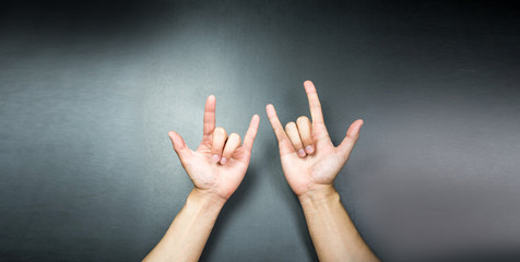 Love hands sign gesture on grey background