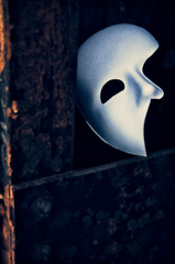 Phantom of the Opera mask on a dark gritty retro vintage steel bridge