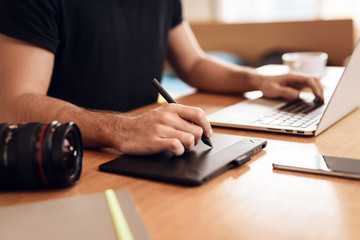 Freelancer bearded man drawing at laptop sitting at desk.