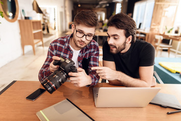 Two freelancer men looking at photos at laptop at desk.