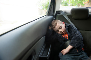 sleeping little child sitting in car in back seat with seat belt