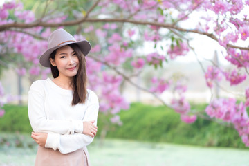 Young woman with cherry blossom garden in Spring day