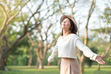 Young woman enjoying Spring and nature in morning in park