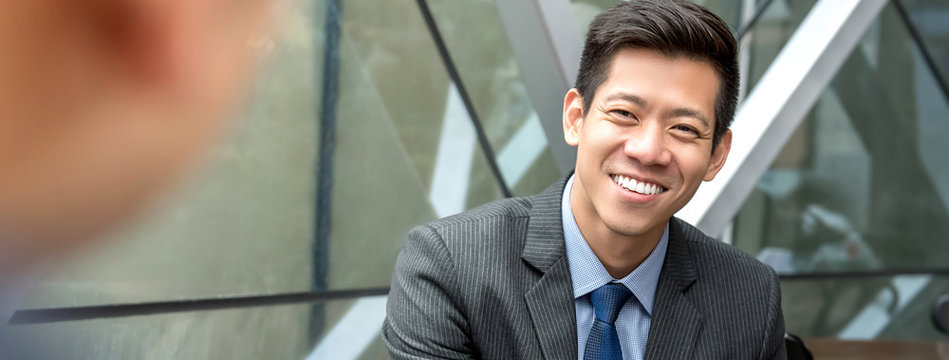 Friendly smiling handsome Asian businessman sitting at office lounge