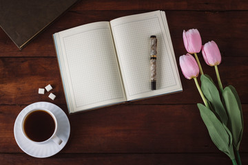 Diary, Cup with Coffee, Tulips, Book on the Dark Wooden Table