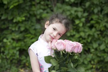 Cute toddler girl holding roses