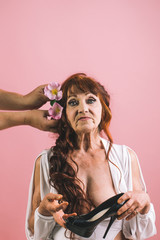 Old woman getting decorated hair with flowers, hairstyle