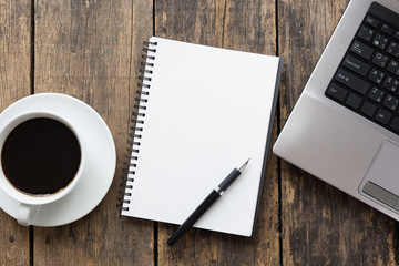 empty notebook with coffee cup and computer on wooden table ,top view