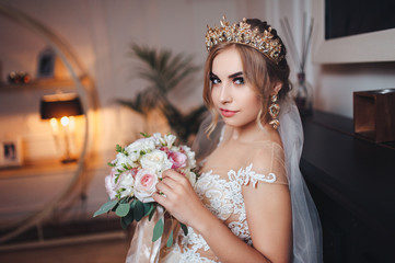 A blond bride with a crown or diadem on her head looks at the camera. Bride in a lace dress with a bouquet.