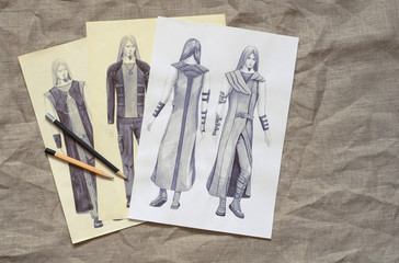 It is the professional design sketch of modern suit. The freehand draft of clothes of Subkultur are on fabric. The ready sample of informal outfits of stylish people executed in pencil is on a paper.