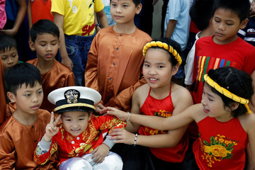A child wears a U.S Navy hat during a visit of sailors to Da Nang SOS Children's Village as part of the visit to Vietnam of U.S aircraft carrier Carl Vinson, in Danang