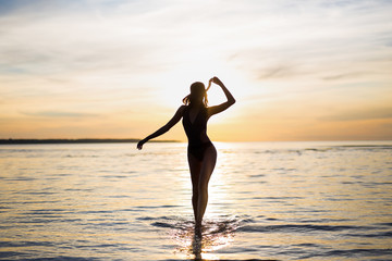 silhouette of slim sexy woman in bikini walking on the beach