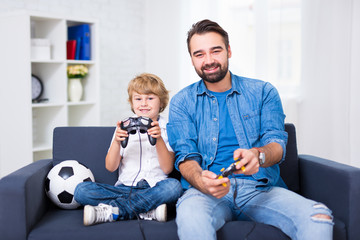 young father and son playing video games at home