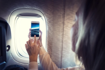 Blond young woman filming video with smartphone