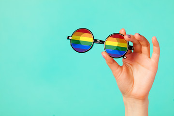 Female hand holding glasses with rainbow flag
