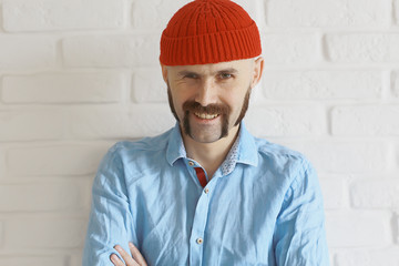 guy with a mustache in a red knitted hat