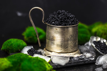 Black caviar in a vintage bowl with lemon close up over dark background, moss