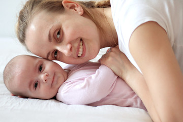 Mother playing with baby and smiling on camera