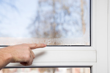 Man's hand pointing to the window glass humidity. Room airing problem.