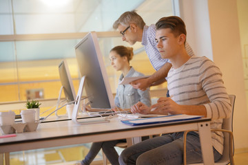 Teacher with students in apprenticeship attending computing class