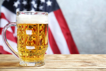 Glass of beer on table against American flag background