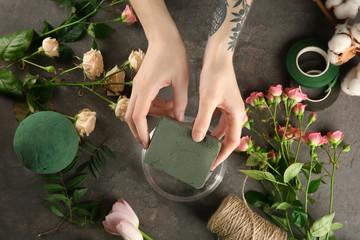 Female florist using sponge for work on grey background