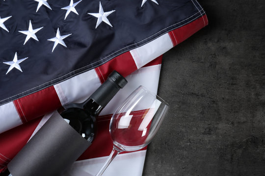 Glass and bottle of wine with American flag on grey background