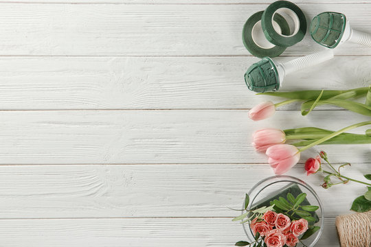 Florist equipment with flowers on wooden background