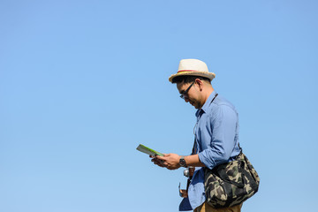 Asian tourist holding map with blue sky in sunny day, lifestyle concept.
