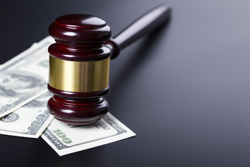 Wooden judge gavel on hundred dollar banknotes over black background