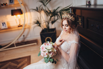 A blond bride with a crown on her head looks at her wedding bouquet. Beautiful bride in the interior. Black piano.