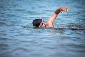 Triathlete man swimming freestyle crawl in ocean - Male triathlon swimmer training for a triathlon