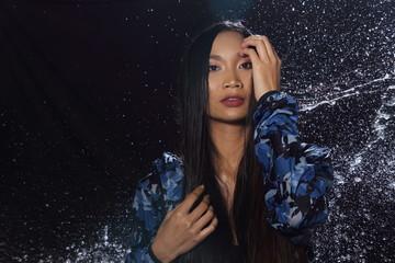 Active Woman rain coat with Water Splash over studio lighting black backgrounds