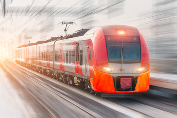High speed train with luminous headlights and rides at high speed at the railway station in the city.