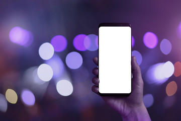 Smart phone in hand with isolated white screen for mockup. Purple bokeh and city lights in background.