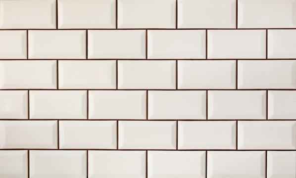 White metro tiles patterned wall. Beige ceramic brick tiles background.