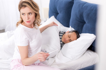 woman with thermometer in hand sitting near ill husband in bed