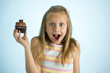 young beautiful happy and excited blond girl 8 or 9 years old holding chocolate cake on her hand looking spastic and cheerful in sugar addiction concept