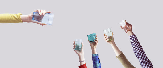 Many different arms raised up holding glass