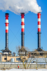 Thermal power plant during winter operation. High chimneys emit a large amount of smoke